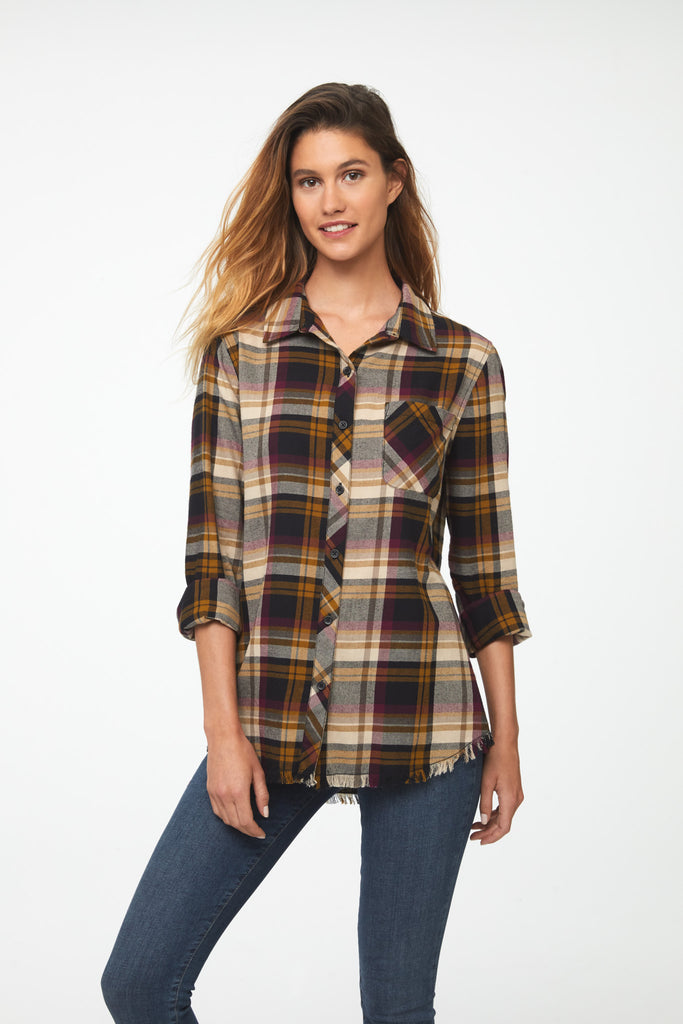 Woman wearing long sleeve, button front flannel shirt in muted yellow, rose and black plaid with frayed hem detailing