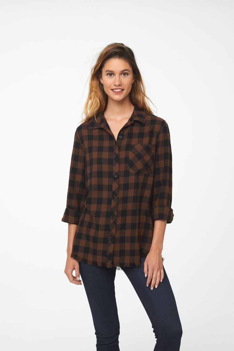 Woman wearing long sleeve, button front flannel shirt in black and brown plaid with frayed hem detailing