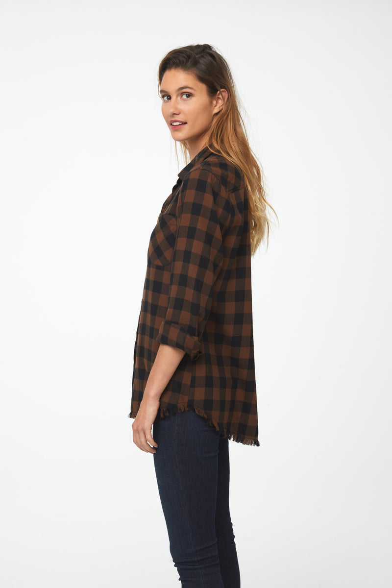 side view woman wearing long sleeve, button front flannel shirt in black and brown plaid with frayed hem detailing