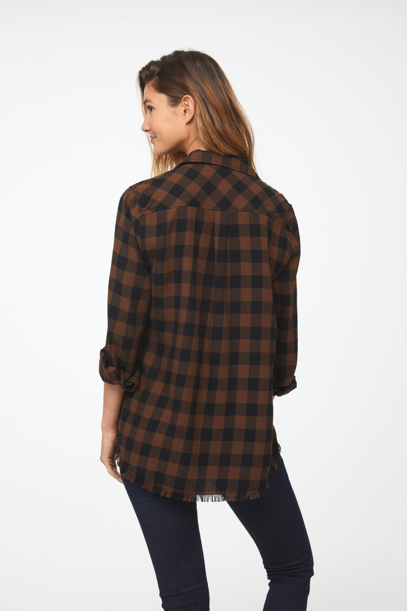 Back view Woman wearing long sleeve, button front flannel shirt in black and brown plaid with frayed hem detailing