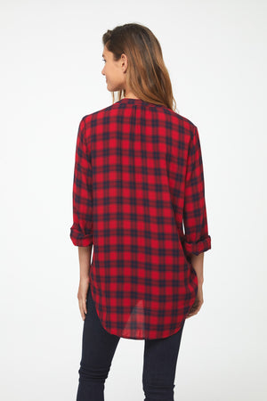 Back of woman wearing Long Sleeve, Relaxed Fit V-Neck Shirt in red and black plaid with curved drop back hem