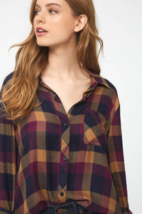 Woman wearing a long sleeve button front shirt in black, red, and gold plaid pattern from the waist up