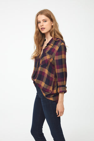 Side profile of a woman wearing a long sleeve, drop back hem shirt in black, red, and gold plaid pattern with cuffed sleeves