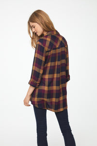 The back of a woman wearing a long sleeve, drop back hem shirt in black, red, and gold plaid pattern with cuffed sleeves