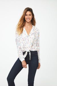 Woman wearing a silky, long sleeve, button front, v-neck in white with colorful confetti pattern blouse with self tie front and drop shoulder