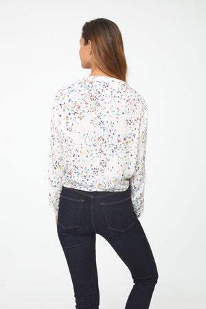 back of woman wearing a silky, long sleeve, button front, v-neck in white with colorful confetti pattern blouse with self tie front and drop shoulder