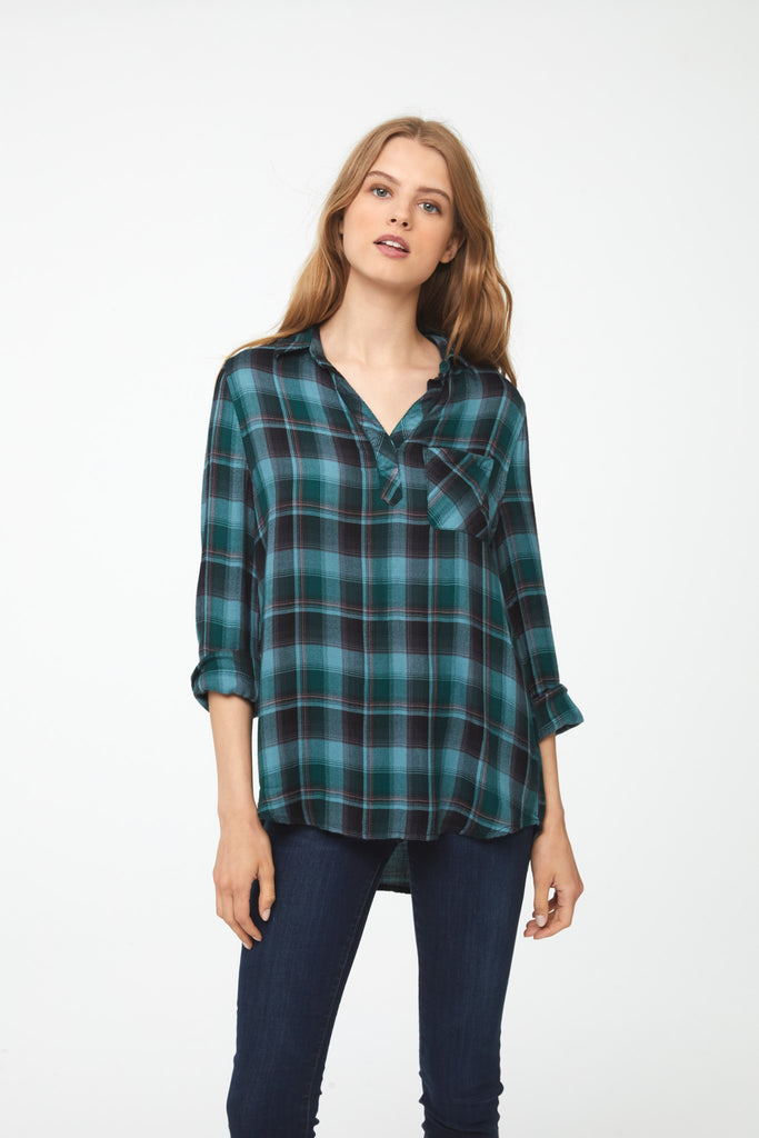 Woman wearing a relaxed, long sleeve V-neck plaid shirt in green and blue hues with brown accents and a single patch chest pocket