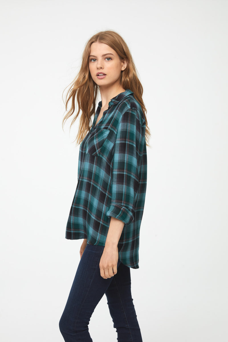 Side view of woman wearing a relaxed, long sleeve V-neck plaid shirt in green and blue hues with brown accents and a single patch chest pocket