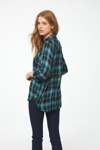 Back view of woman wearing a relaxed, long sleeve V-neck plaid shirt in green and blue hues with brown accents and drop back hem