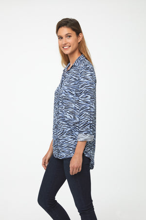 side view of woman wearing a light blue, long sleeve, button-down blouse in a modern zebra print with a single chest pocket and drop back hem