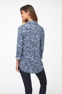 back view of woman wearing a light blue, long sleeve, button-down blouse in a modern zebra print with a single chest pocket and drop back hem