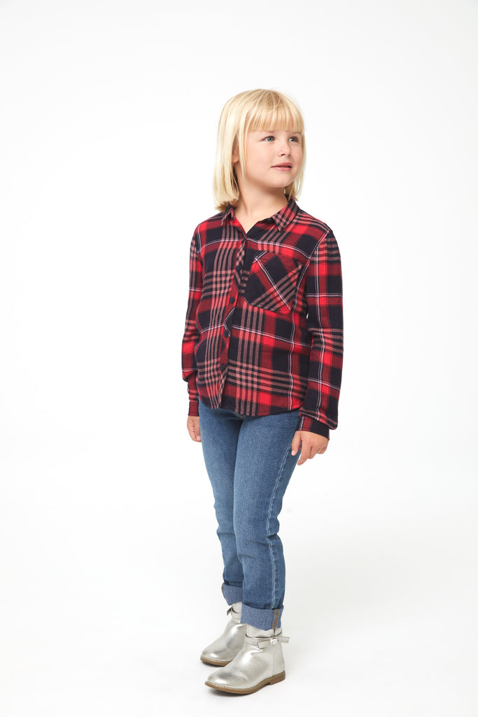 Girl wearing a long sleeve, button-down plaid shirt in red and black with white accents and a single front patch pocket and curved hem