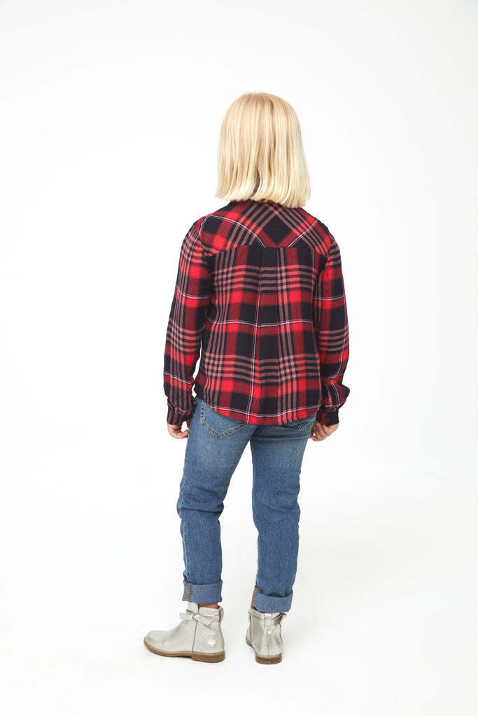 Back of girl wearing long sleeve, button-down plaid shirt in red and black with white accents and a single front patch pocket and curved hem