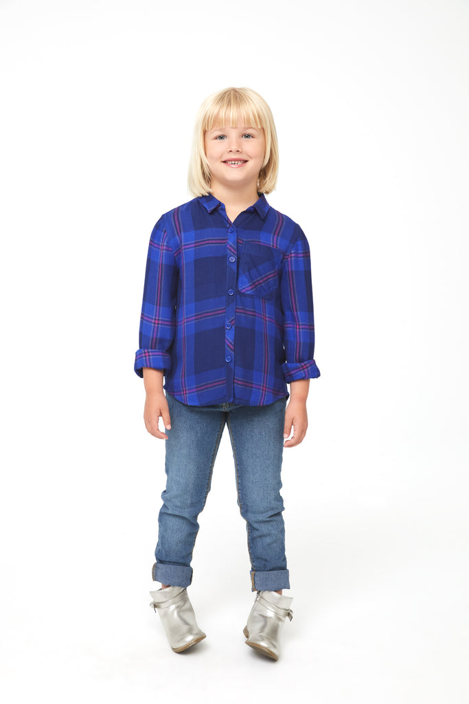 Girl wearing a long sleeve, button-down blue plaid shirt with magenta accents, a single front patch pocket and curved hem