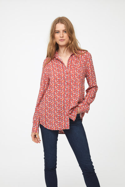 woman wearing a coral, long sleeve button-down blouse with bird print, single chest pocket and drop back hem