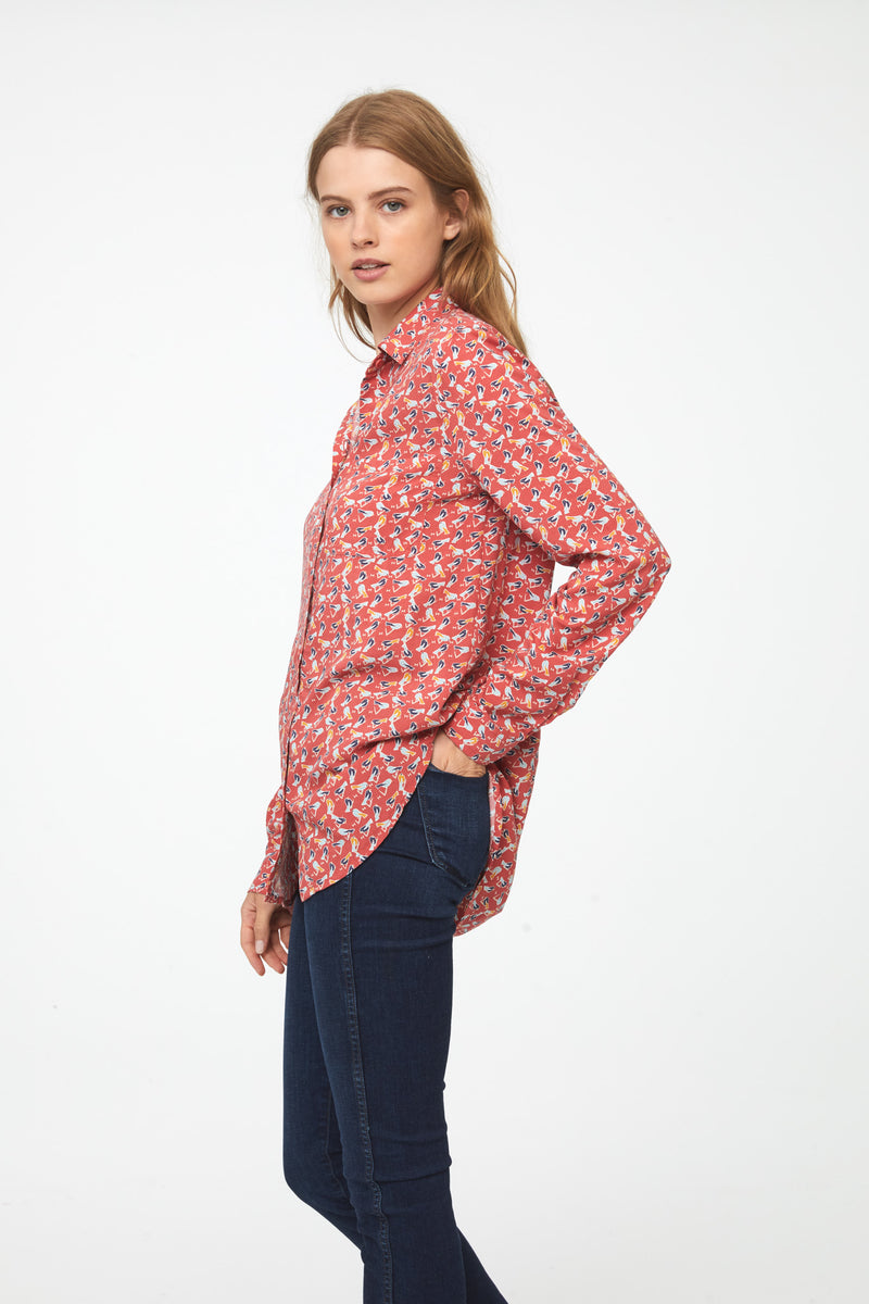 side view of woman wearing a coral, long sleeve button-down blouse with bird print, single chest pocket and drop back hem