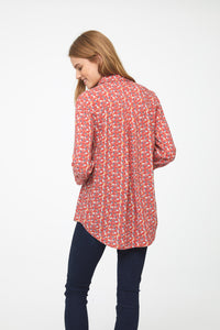 back view of woman wearing a coral, long sleeve button-down blouse with bird print, single chest pocket and drop back hem