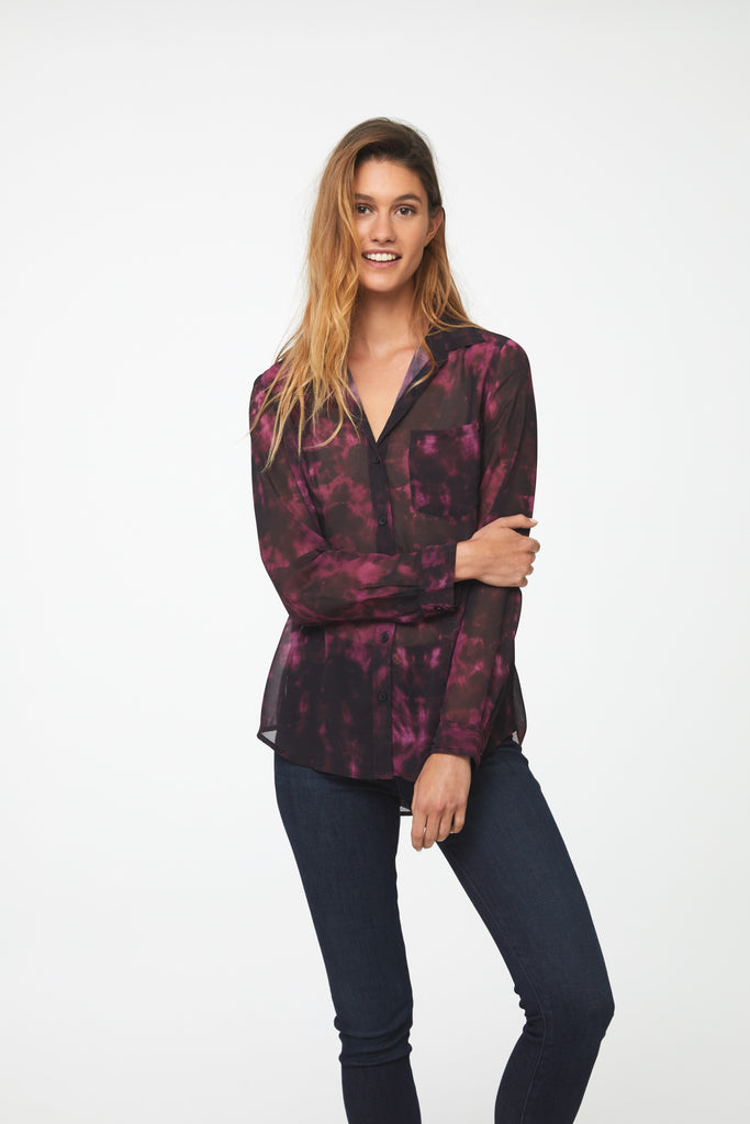 Woman wearing a semi-sheer, deep red tie-dye print button down shirt with a single patch pocket and curved hem