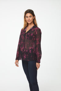 Side view of Woman wearing a semi-sheer, deep red tie-dye print button down shirt with a single patch pocket and curved hem