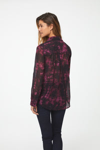 back view of woman wearing a semi-sheer, deep red tie-dye print button down shirt with a single patch pocket and curved hem