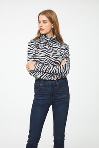 Woman wearing long sleeve zebra-print turtle neck sweater