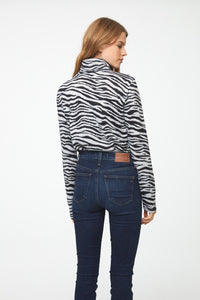 Back of woman wearing long sleeve zebra-print turtleneck sweater