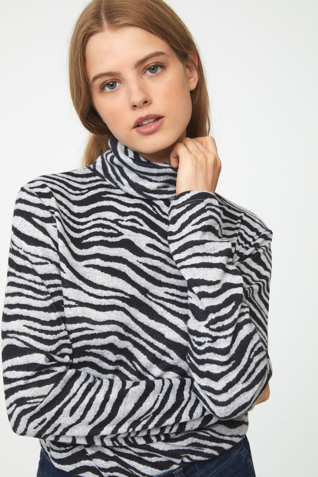 Woman wearing long sleeve zebra-print turtleneck sweater