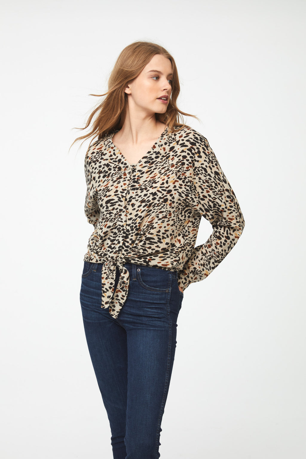 woman wearing a long sleeve, button front, V-neck animal print blouse with tie front at waist
