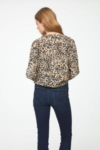 Back of woman wearing a long sleeve, button front, V-neck animal print blouse with tie front at waist