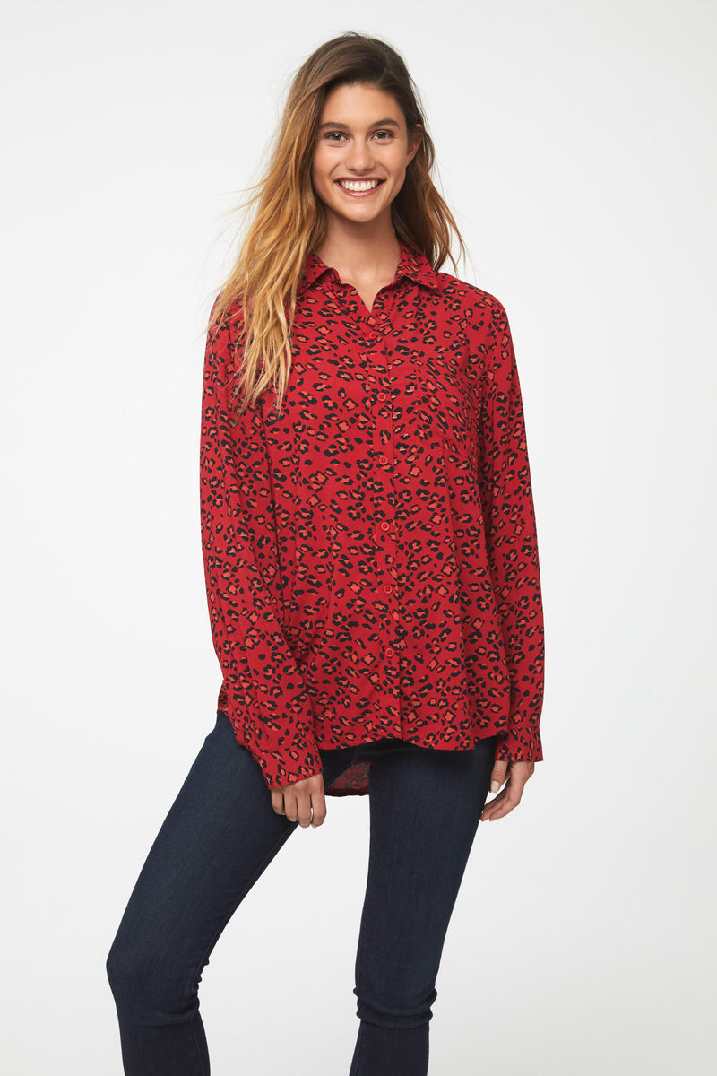 Woman wearing a classic, long sleeve button down, collared shirt with single chest pocket and drop hem back in red leopard print