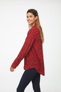 side view of Woman wearing a classic, long sleeve button down, collared shirt with single chest pocket and drop hem back in red leopard print