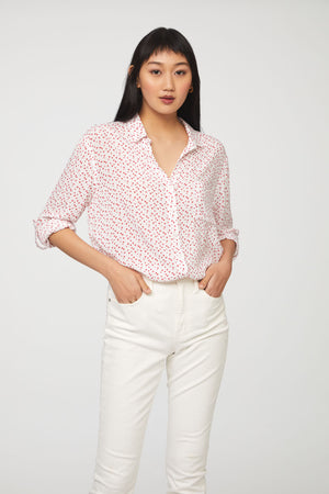 woman wearing a long sleeve, button-down,white and red heart print shirt with single chest pocket