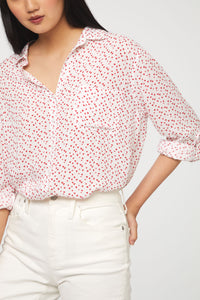 close up of woman wearing a long sleeve, button-down,white and red heart print shirt with single chest pocket