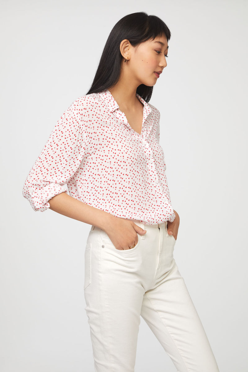 side view of woman wearing a long sleeve, button-down,white and red heart print shirt with single chest pocket
