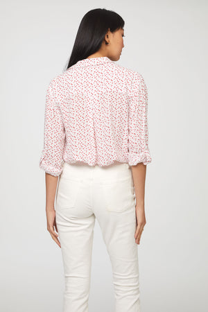 back view of woman wearing a long sleeve, button-down, white and red heart print shirt with single chest pocket