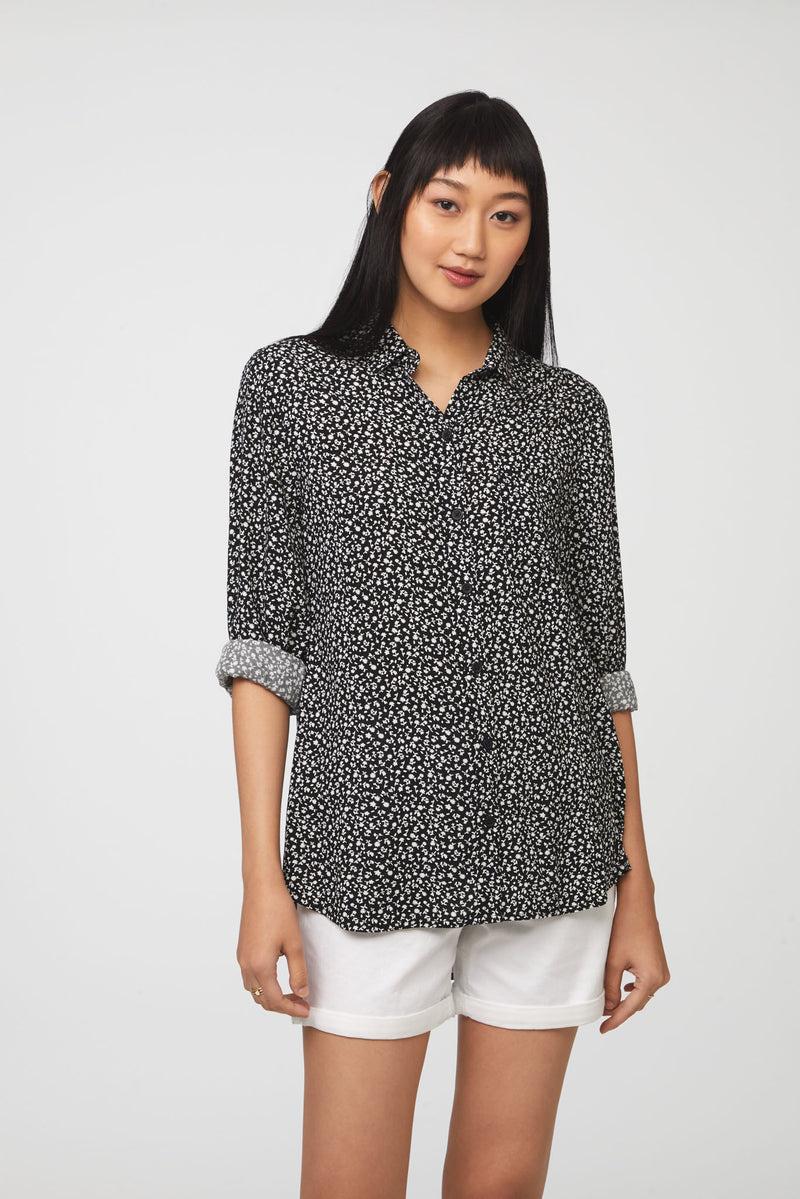 woman wearing a long sleeve, button-down, black and white floral shirt with single chest pocket