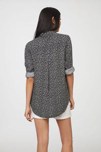 back view of woman wearing a long sleeve, button-down, black and white floral shirt with single chest pocket