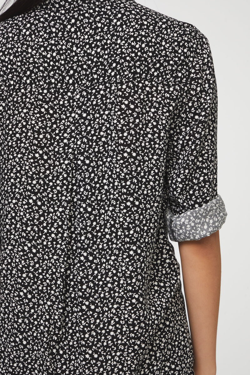 close up view of woman wearing a long sleeve, button-down, black and white floral shirt with single chest pocket