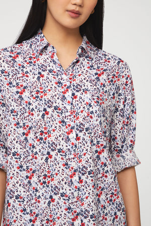 close up of woman wearing a long sleeve, button-down, red, white, and blue floral shirt with single chest pocket