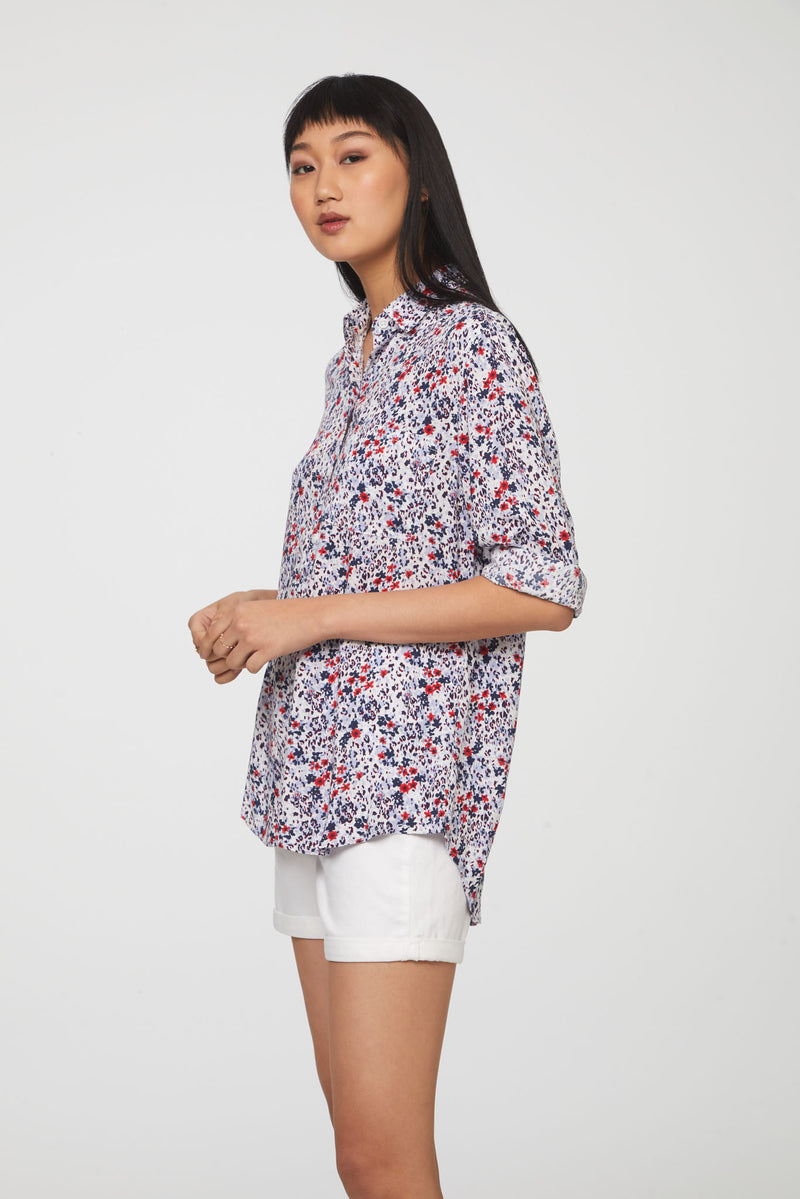 side view of woman wearing a long sleeve, button-down, red, white, and blue floral shirt with single chest pocket