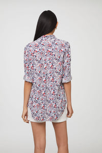 back view of woman wearing a long sleeve, button-down, red, white, and blue floral shirt with single chest pocket