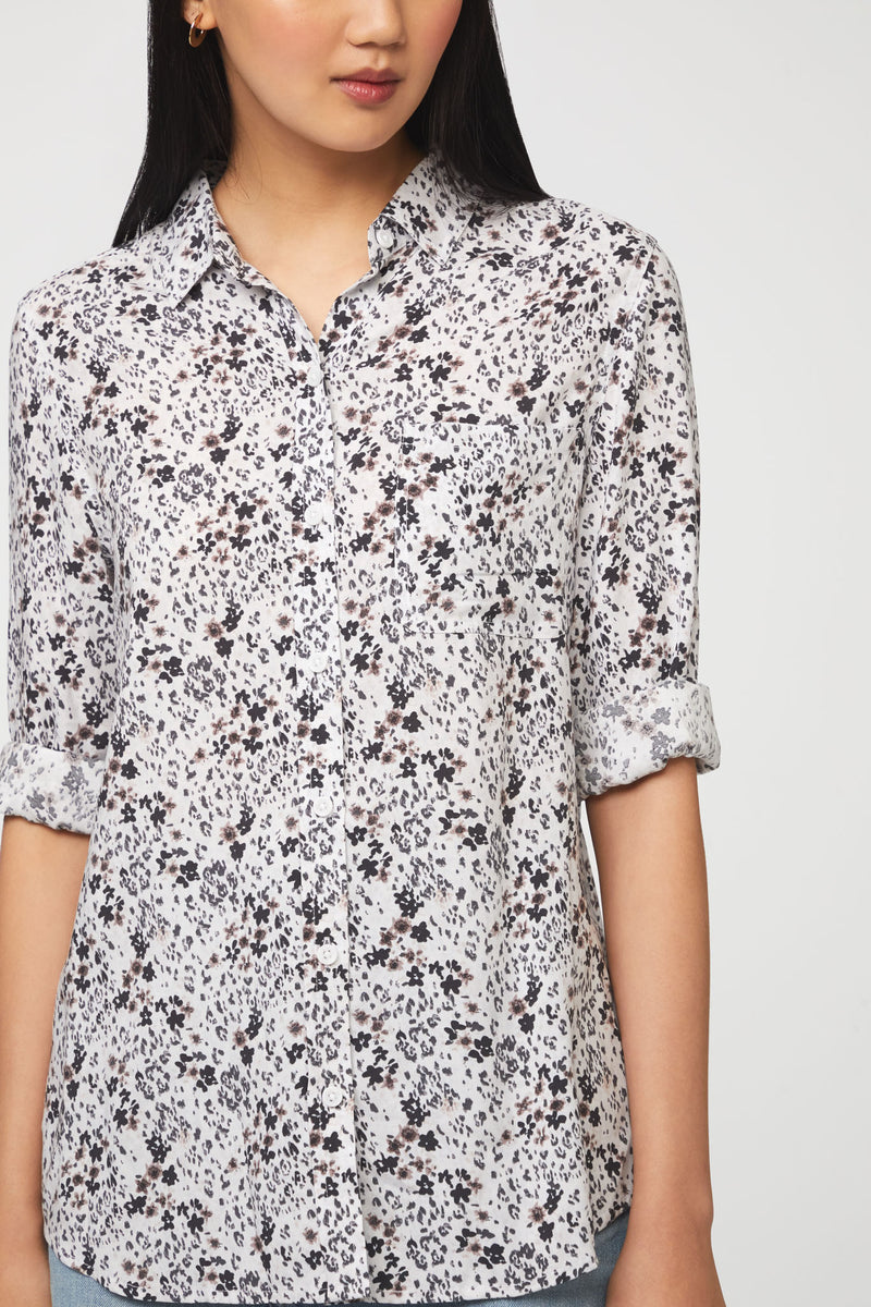 close up of woman wearing a white and brown floral print, long sleeve, button-down blouse with single chest pocket and drop back hem