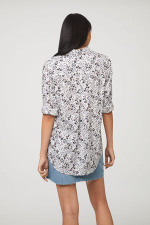 back view of woman wearing a white and brown floral print, long sleeve, button-down blouse with single chest pocket and drop back hem