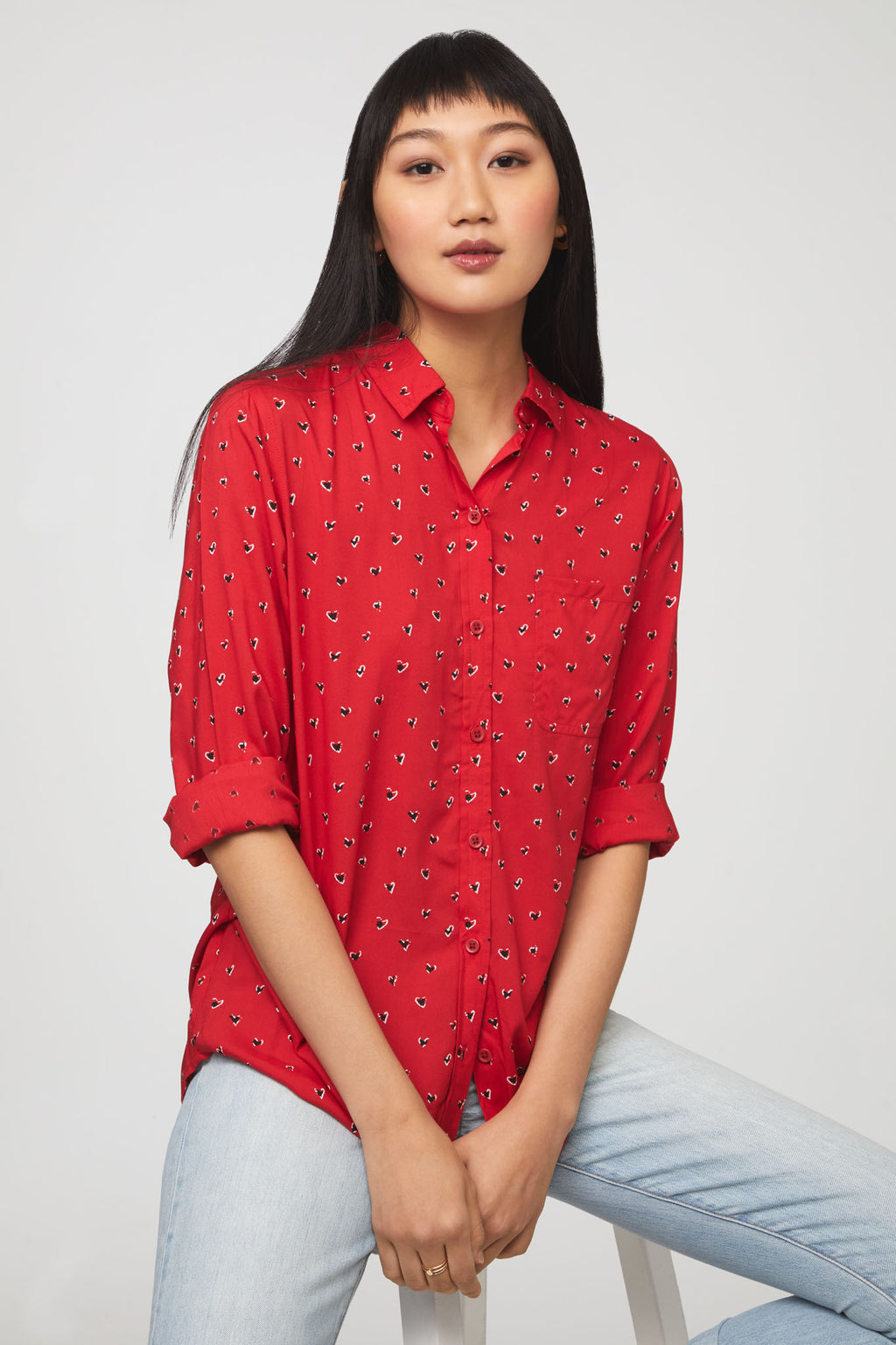 woman wearing a heart printed long sleeve, button-down, red shirt with single chest pocket