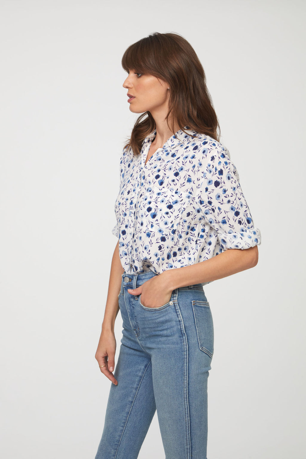 side view of woman wearing a white and blue floral print, long sleeve, button-down blouse with single chest pocket and drop back hem