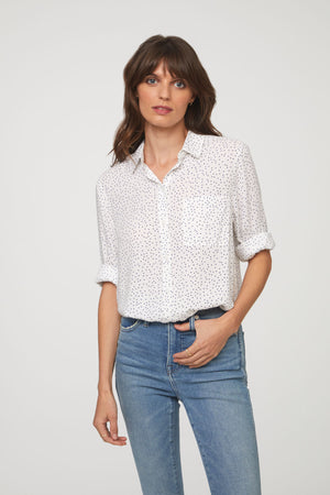 woman wearing a long sleeve, button-down, white and black polka dot shirt with single chest pocket