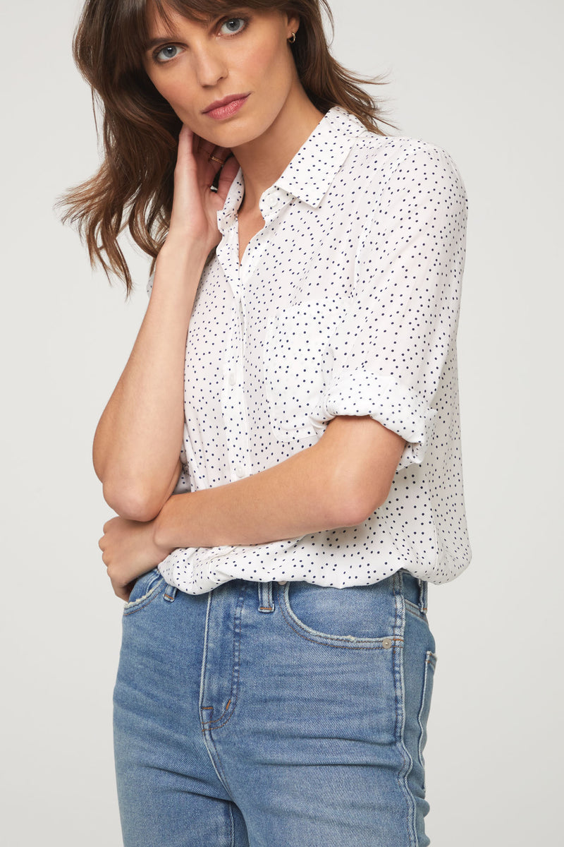 detail view of woman wearing a long sleeve, button-down, white and black polka dot shirt with single chest pocket