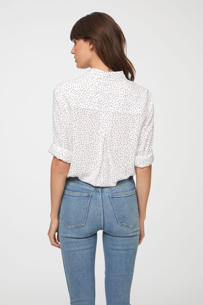 back view of woman wearing a long sleeve, button-down, white and black polka dot shirt with single chest pocket