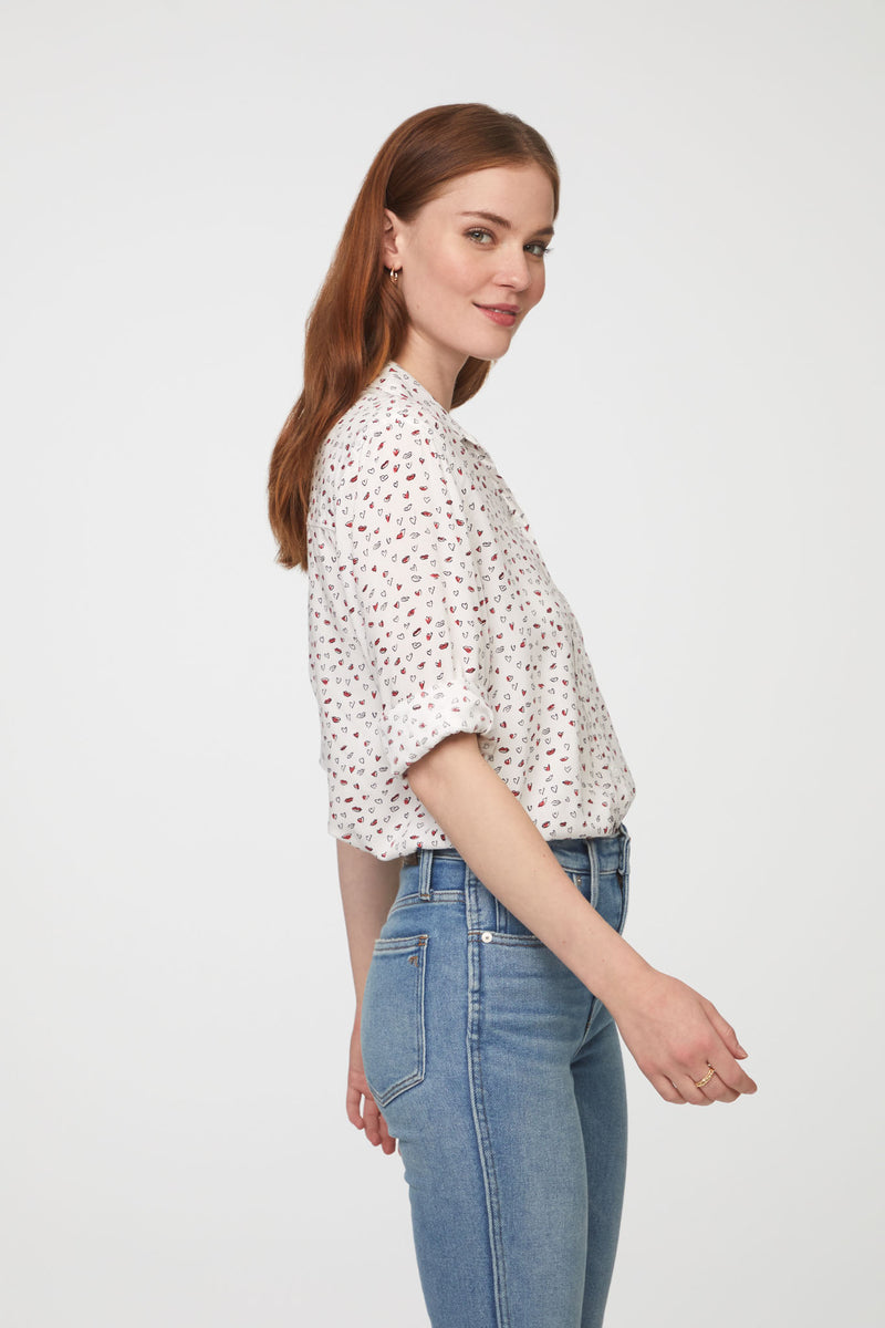 side view of woman wearing a long sleeve, button-down, white shirt with heart print and single chest pocket