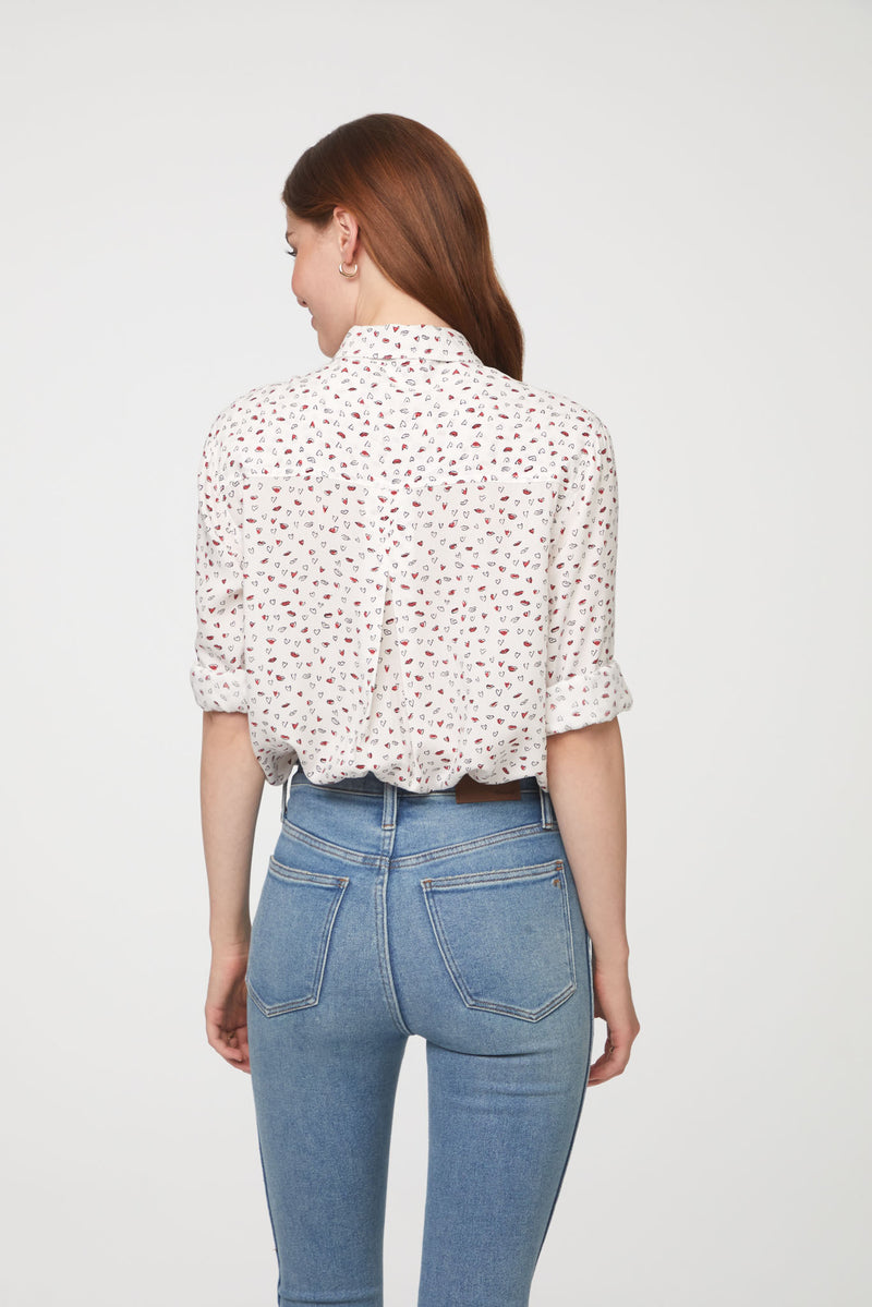 back view of woman wearing a long sleeve, button-down, white shirt with heart print and single chest pocket